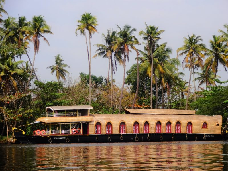 A huge houseboat on the Alleppey backwaters, surrounded by tall coconut and palm trees