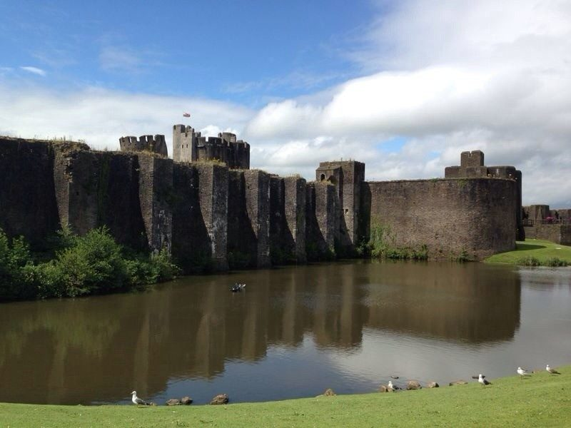 Caerphilly Castle and the surrounding moat on a sunny day