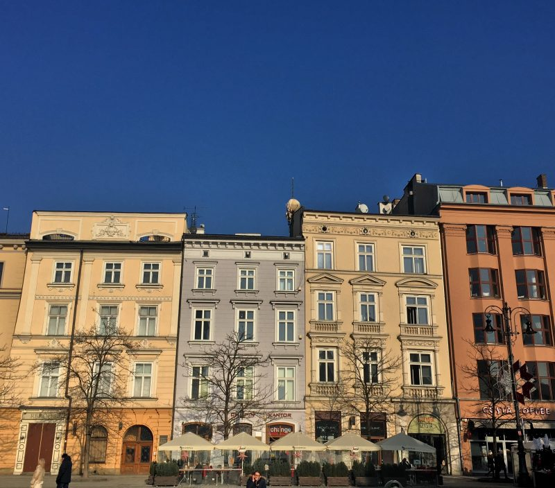colourful buildings in Krakow's main square, one of them is a Costa Coffee