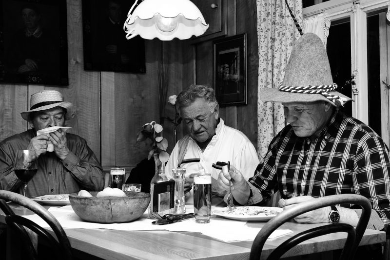 Three old men eating dinner and drinking beer at a table while wearing hats