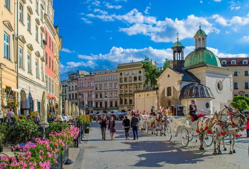 horse drawn carriages in the main square at Krakow - one of the top things to do in Krakow
