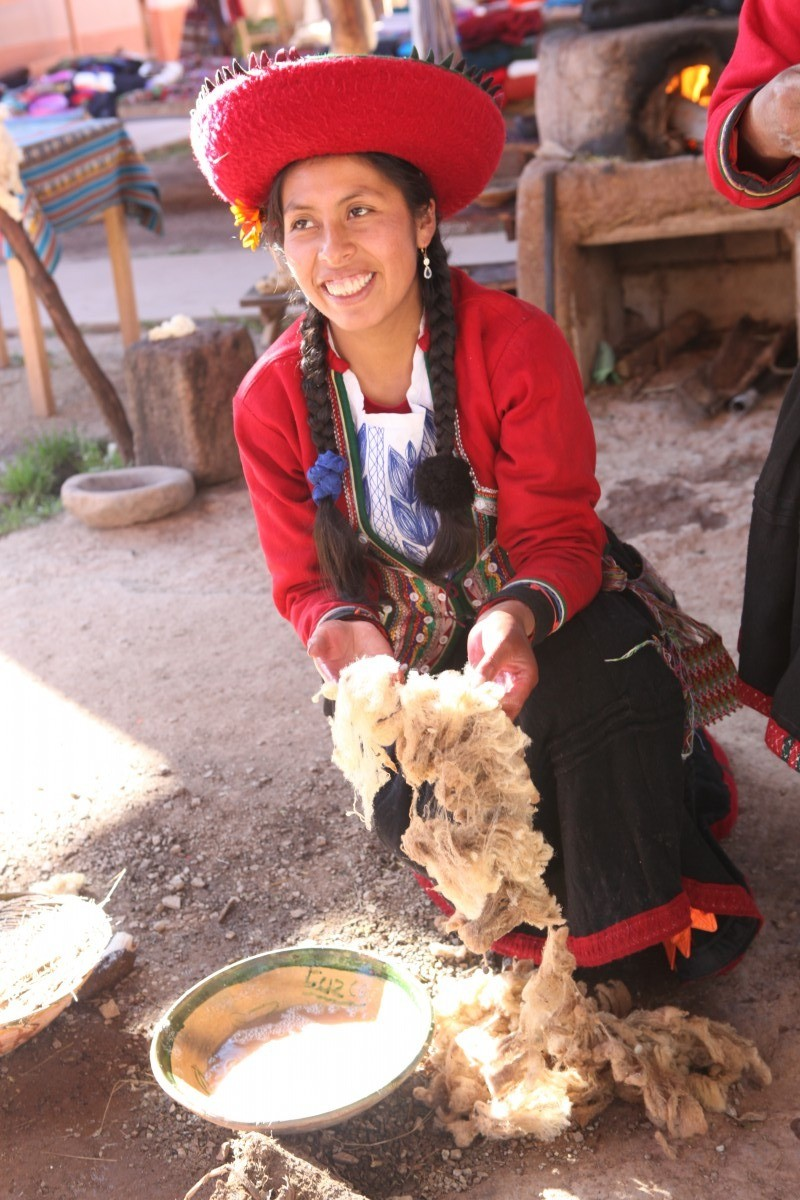 a traditionally dressed Peruvian lady preparing alpaca wool at the Chinchero Handweaving Coop