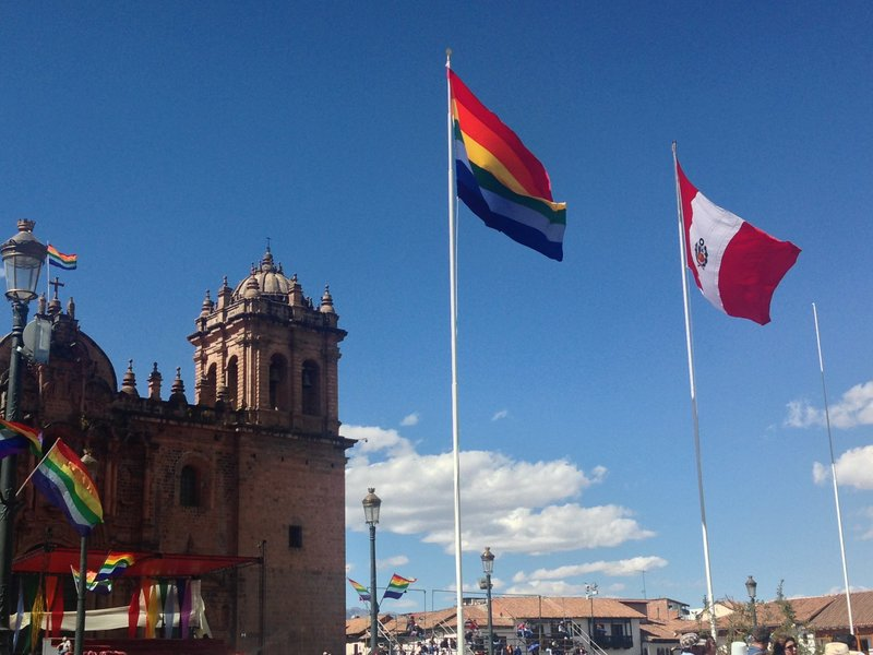The national flag of Peru and regional flag of Cusco flying over the Plaza de Armas on Dia de la Independencia in Cusco