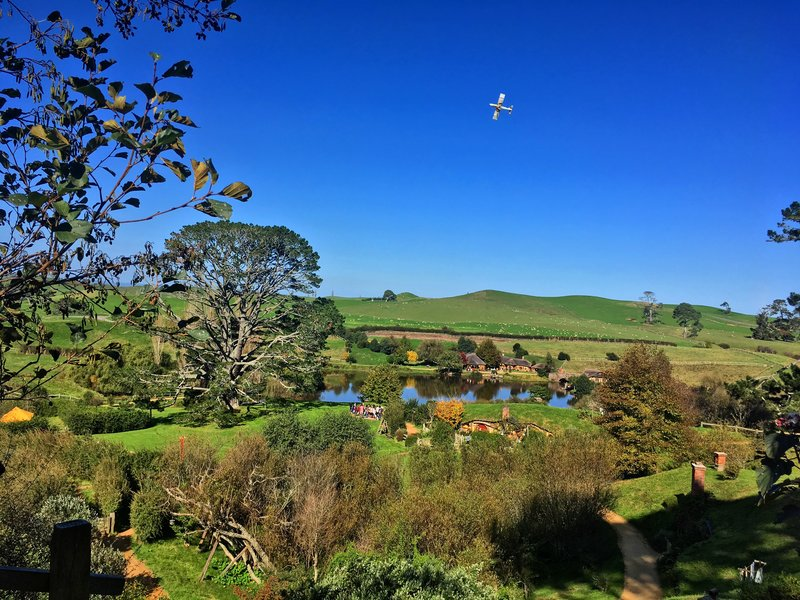 The view of Hobbiton and surrounding fields with a fertilisation plane flying overhead
