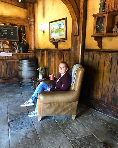 girl sat on chair drinking ginger beer from a stein in The Green Dragon Inn, Hobbiton