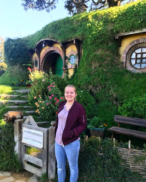 girl in maroon coat standing outside Bag End at Hobbiton Movie Set in New Zealand